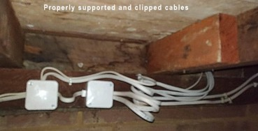 Properly clipped cables under a floor